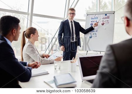 Elegant young businessman pointing at data on whiteboard during explanation of chart