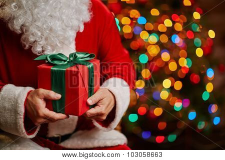 Red package bound by silk green ribbon held by Santa Claus