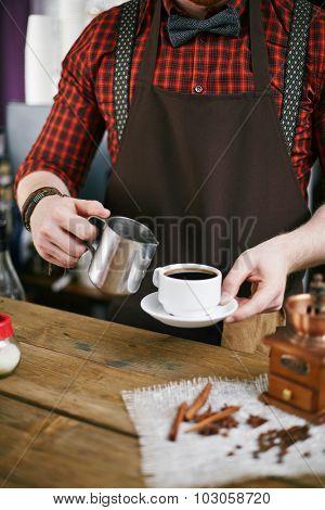 Barista in uniform holding cup black coffee and steel mug