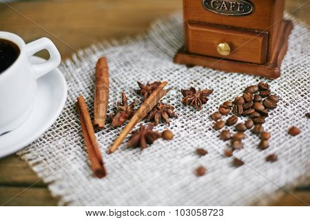 Wooden coffee grinder, coffee grains, flavourings and cup of coffee