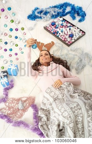 Young woman lying on floor surrounded by christmas ornaments, wearing reindeer antler.