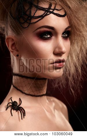 Closeup portrait of young woman in halloween makeup with spider on shoulder, looking away.