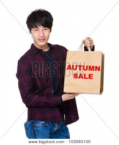 Young Man hold with shopping bag for showing phrase of autumn sale