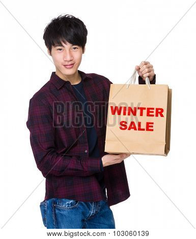 Young Man hold with shopping bag for showing phrase of winter sale