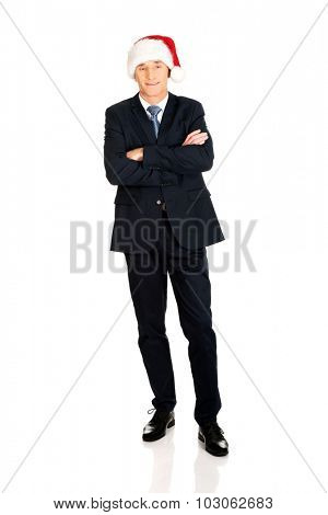 Full length businessman with folded arms wearing santa hat.