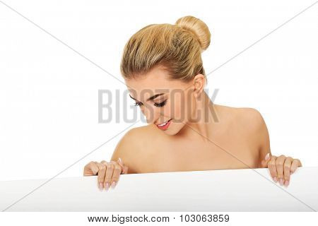 Nude woman holding blank banner,isolated on white.