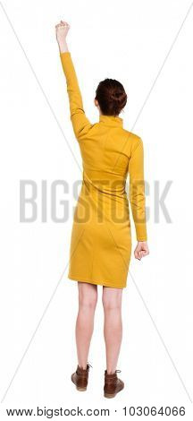 Back view of  woman.  Raised his fist up in victory sign.  Rear view people collection.  backside view of person. Girl in mustard strict dress raised his right hand with the palm clutched in his fist.