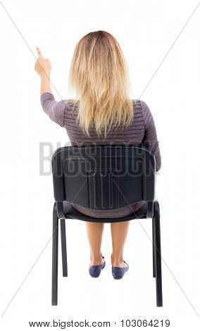 back view of young beautiful  woman sitting on chair and pointing. backside view of person.  Isolated over white background. The girl in the purple dress sitting on a chair pointing to the left.