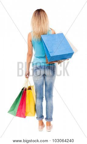 back view of woman with shopping bags. backside view of person.  Rear view people collection. Isolated over white background. girl in jeans and a blue shirt is throwing his purchases on his shoulder.