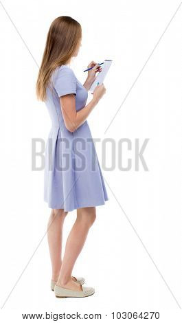 back view of  stands woman takes notes in a notebook. girl  watching. Rear view people collection.    Isolated over white background. The girl in a blue dress stands sideways and draws in a notebook.