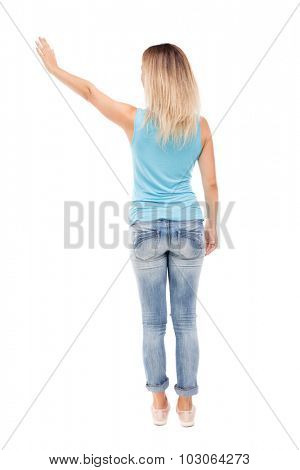 Back view beautiful woman welcomes. Young teenager girl in jeans hand waving from. Rear view people collection. Isolated over white background. girl in jeans and a blue shirt with his left hand waving