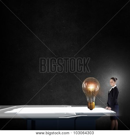 Young businesswoman looking at glass light bulb