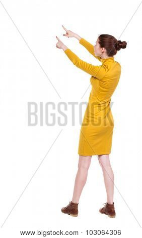 Back view of  pointing woman. beautiful girl. Rear view people collection.  backside view of person.  Isolated over white background. Girl in mustard strict dress stands sideways and two hands shows.