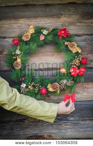 Human Arm Holding Decorative Red Bow Near Outdoor Christmas Wreath At Log Cabin Wall Background