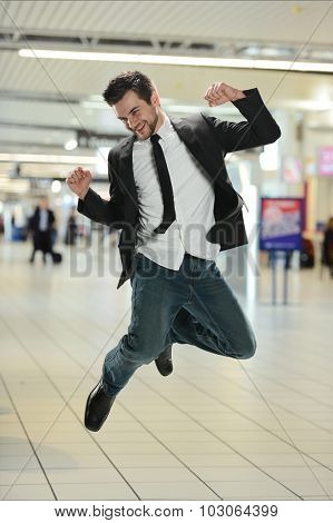 Young Businessman jumping of joy inside the airport terminal