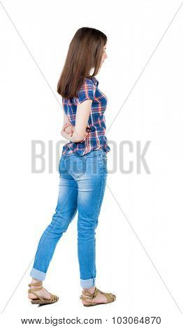 back view of standing young beautiful  woman. girl watching. Rear view people collection. Isolated over white background. Girl in a blue plaid shirt with short sleeves is hands clasped behind his back