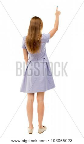 Back view of  pointing woman. beautiful girl. Rear view people collection.  backside view of person.  Isolated over white background. The girl in a blue dress is pointing upwards.