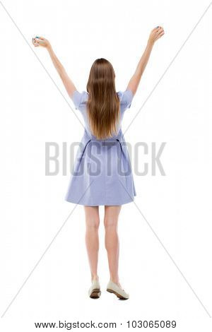 Back view of beautiful woman welcomes. Young teenager girl in jeans hand waving from. Rear view  people collection.  Isolated over white background. Girl in blue raised his hands to heaven.