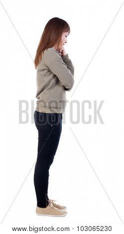 back view standing young beautiful woman. girl watching. Rear view people collection.  backside view person. Isolated over white background. Girl standing sideways, wondering resting his fist on cheek