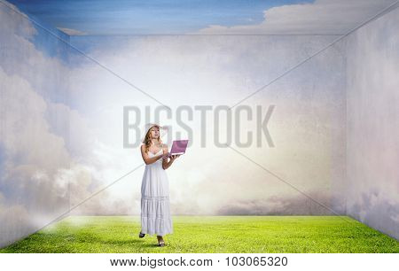 Young lady in white long dress and hat with laptop in hands