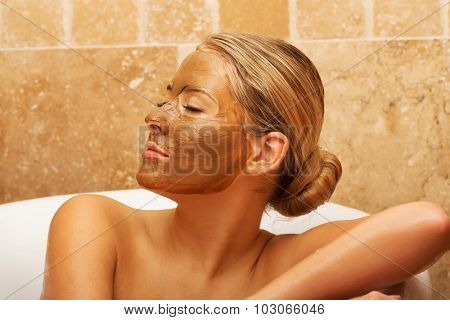 Relaxed woman sitting in a bath with closed eyes and face mask.