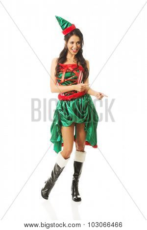 Full length woman wearing elf clothes pointing to the right.