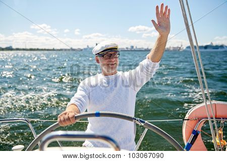 sailing, age, tourism, travel and people concept - happy senior man in captain hat on steering wheel and waving hand sail boat or yacht floating in sea