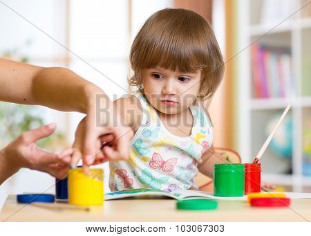 Teacher and child painting together at nursery with paintbrushes and watercolors
