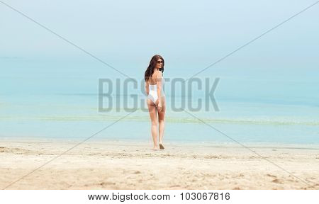 summer vacation, tourism, travel, holidays and people concept -young woman in swimsuit walking on beach from back