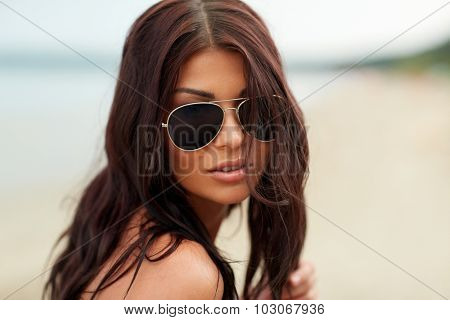 summer vacation, tourism, travel, holidays and people concept -face of young woman with sunglasses on beach
