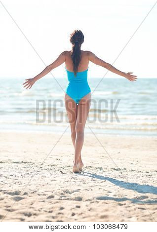 summer vacation, tourism, travel, holidays and people concept -young woman in swimsuit posing on beach from back