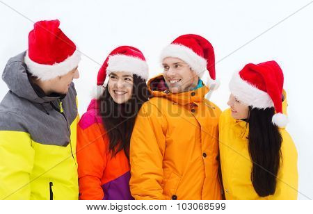 winter holidays, christmas, friendship and people concept - happy friends in santa hats and ski suits outdoors