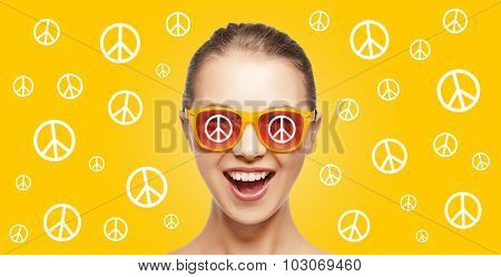 people, summer accessories and pop art concept - happy screaming teenage hippy girl in shades over yellow background with peace signs