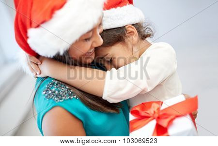 christmas, holidays, family, childhood and people concept - happy mother and little girl in santa hats cuddling at home