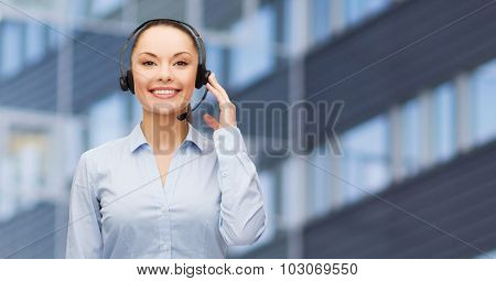 business, people, technology and communication concept - happy asian female helpline operator in headset over city office building background