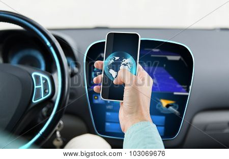 transport, business trip, technology and people concept - close up of young man hand with globe on smartphone screen driving car