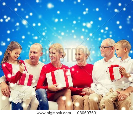 family, holidays, generation, christmas and people concept - smiling family with gift boxes sitting on couch over blue snowy background