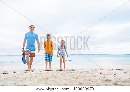 Father and kids with snorkeling equipment enjoying beach vacation