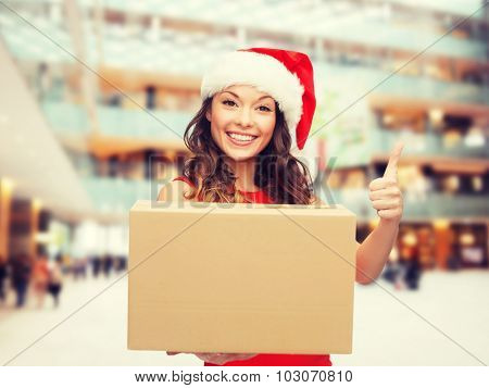 christmas, winter holidays, delivery, gesture and people concept - smiling woman in santa helper hat with parcel box showing thumbs up over shopping center background