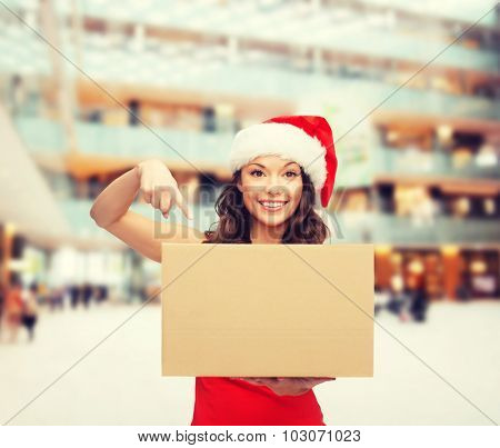 christmas, winter, holidays, delivery and people concept - smiling woman in santa helper hat with parcel box over shopping center background