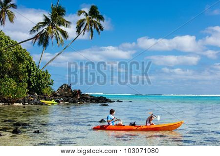 Father and daughter kayaking at tropical ocean