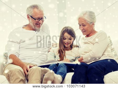 family, generation, education and people concept - smiling grandfather, granddaughter and grandmother with book or photo album sitting on couch at home