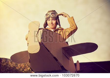 Eight-year boy playing with a cardboard airplane outdoor over sky background. Childhood. Fantasy, imagination.