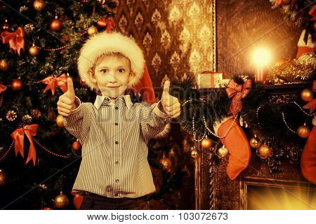 Cute seven year old boy stands with a gift by the Christmas tree at home. The magic of Christmas.