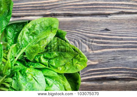 Fresh green spinach leaves in colander on wooden background