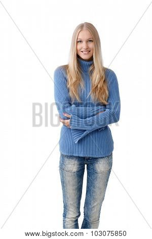 Happy young blonde woman standing arms crossed, wearing jeans and pullover.