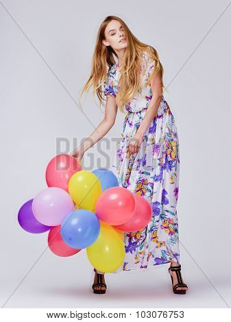 fashion studio photo of beautiful model woman with blond hair in dress holding colorful balloons