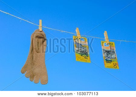 Odd Socks And Bank Note Hanging On A Clothesline On A Sky Background.