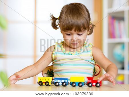 Cute kid girl playing wooden trains toy