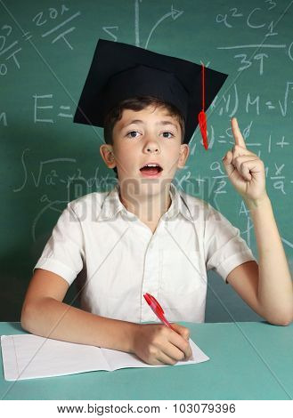Boy In Graduation Cap On The Blackboard Background Close Up Portrait